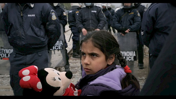 A young girl holds her stuffed Minnie Mouse as Greek police stand blocking the crossing into Macedonia. Thousands of refugees were stranded for months along this border in early 2016.