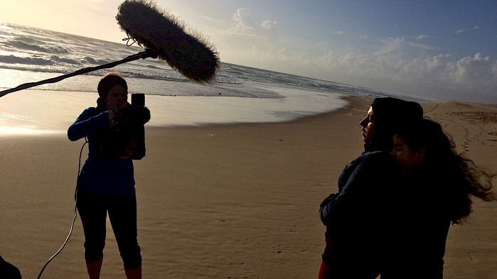 A crew films Zahra and her daughter on a beach in Portugal.
