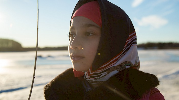 Sahar looks out over a frozen lake in Sweden.