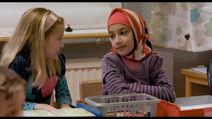 Sahar speaks to a new friend in a classroom in Sweden.