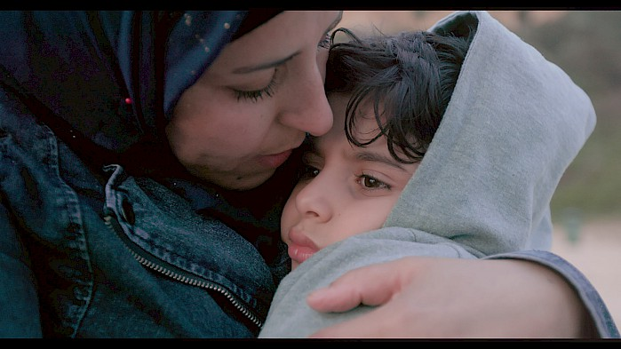 Zahra holds her youngest son on the beach. She tells him that she hid him inside her heart while they crossed the Aegean Sea.