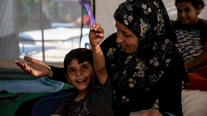 Zahra and her son enjoy a happy moment in a refugee camp in Greece.